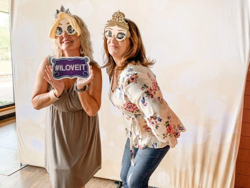 two women in a photo booth at a lakes area professional women's event