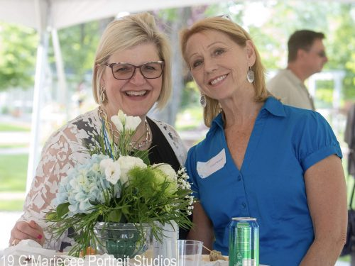two women smiling at a lakes area professional women's event